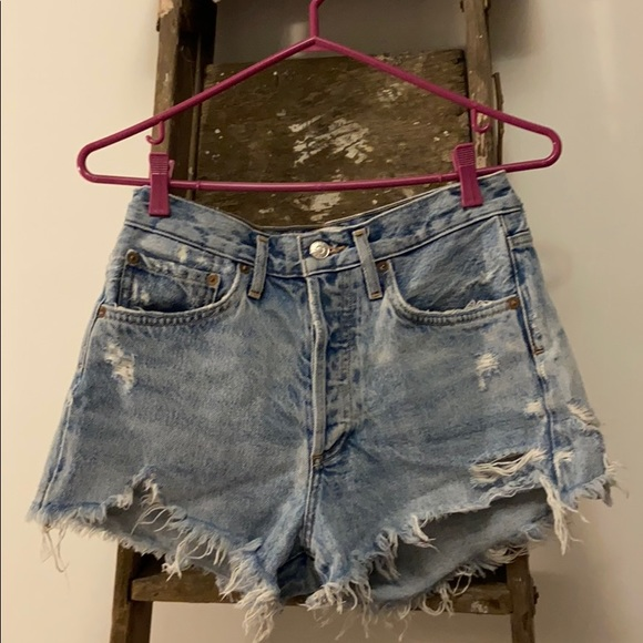 Agolde light denim ripped jean shorts.